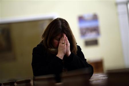 A woman prays at Saint Rose of Lima Roman Catholic Church near Sandy Hook Elementary School, where a gunman opened fire on school children and staff in Newtown, Connecticut December 14, 2012. REUTERS/Joshua Lott