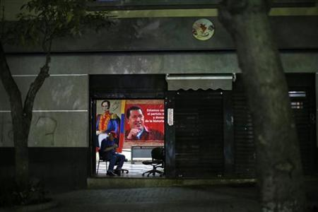 A man sits at the entrance of a building with a poster of Venezuelan President Hugo Chavez in Caracas December 14, 2012. President Chavez is recovering ''satisfactorily'' from his cancer surgery in Cuba although the process remains slow, Information Minister Ernesto Villegas said on Friday. Reading the latest of regular government updates on the socialist leader's condition, three days after his operation, Villegas said the 58-year-old president had communicated with relatives and sent greetings to all Venezuelans.REUTERS/Jorge Silva (VENEZUELA - Tags: POLITICS HEALTH)