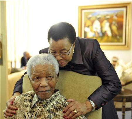 Former South African President Nelson Mandela relaxes with his wife Graca Machel at home in Houghton May 16, 2011. REUTERS/Elmond Jiyane/GCIS - Government Communication and Information System/Handout/Files