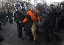 Police officers detain an opposition activist during unauthorised rally in central Moscow December 15, 2012. REUTERS/Mikhail Voskresensky