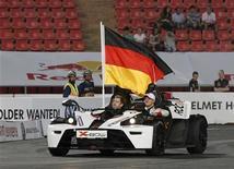 Alemania, representada en la Fórmula Uno por los campeones del mundo Sebastian Vettel y Michael Schumacher, ganó la Carrera de Campeones por sexto año consecutivo en Bangkok el sábado. En la imagen, Vettel (izq) y Schumacher, en un coche con la bandera de Alemania durante la presentación de la Carrera de Campeones. REUTERS/Chaiwat Subprasom