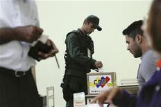 Los venezolanos acudían el domingo a las urnas para elegir gobernadores en unos comicios marcados por la ausencia del presidente Hugo Chávez, quien convalece en Cuba de una operación por el cáncer que padece y que podría poner fin a su gobierno de 14 años. En la imagen, un soldado vota en las elecciones regionales de Venezuela, el 16 de diciembre de 2012. REUTERS/Carlos García Rawlins
