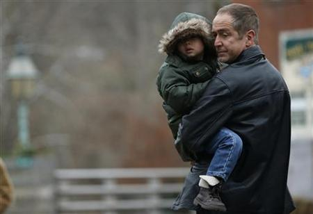 A father carrying a boy, pauses at a makeshift memorial near the Sandy Hook Elementary School for the victims of a school shooting in Newtown, Connecticut early December 16, 2012. REUTERS/Mike Segar