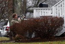 Membro da equipe da SWAT de Connecticut se posiciona perto de igreja que sofreu ameaça de bomba, perto do local do massacre que matou 20 crianças, na sexta-feira.