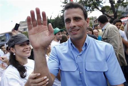 Miranda state Governor and candidate for re-election Henrique Capriles (C) greets supporters before casting his vote during regional election in Caracas December 16, 2012. REUTERS/Carlos Garcia