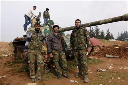 Free Syrian Army fighters pose at a tank after capturing the Military Infantry School following heavy clashes with forces loyal to President Bashar al-Assad in Aleppo December 16, 2012. REUTERS/Zain Karam
