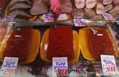 Торговец продает икру и рыбу на рынке в Санкт-Петербурге 5 апреля 2012 года. Компания Русское море продала завод по производству пресервов из рыбы и морепродуктов в Ногинске инвестору за $52 миллиона, сообщила группа в понедельник. REUTERS/Alexander Demianchuk