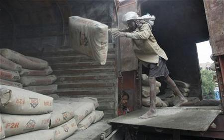 A labourer unloads cement sacks from the wagon of a train at a yard in Kolkata June 25, 2012. REUTERS/Rupak De Chowdhuri/Files