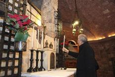 """Premiê italiano, Mario Monti, segura vela diante do túmulo de São Franciso de Assis, em Assisi. Monti postou-se diante da tumba de são Francisco e rezou para o homem que pregava aquilo que os franciscanos chamam de """"o dom do discernimento"""". 15/12/2012 REUTERS/Divulgação"""