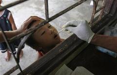 """La financiación mundial para combatir la malaria se ha estancado en los últimos dos años, lo que amenaza con dar al traste con los que según la Organización Mundial de la Salud han sido """"logros recientes remarcables"""" en la lucha por controlar una de las principales enfermedades infecciosas del mundo. En la imagen, un trabajador sanitario coloca un termómetro en la boca de un niño en una clínica de la malaria en Sai Yoke, Tailandia, el 26 de octubre de 2012. REUTERS/Sukree Sukplang"""