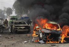A police officer and a citizen walk towards a burning car after a bomb attack, at Fauji Market in Peshawar December 17, 2012. REUTERS/Ameerzada Afridi