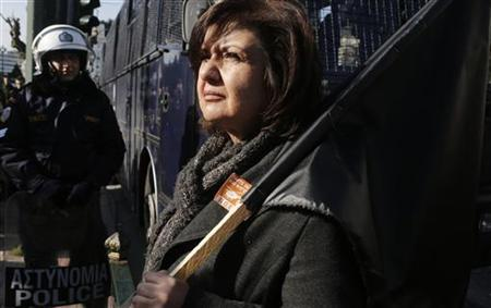 A woman holds a black flag during a rally against state sector layoffs demanded by the country's international lenders, outside the parliament in central Athens December 14, 2012. REUTERS/John Kolesidis