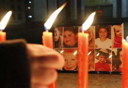 An Albanian boy lights candles to pay respect to victims of Sandy Hook Elementary School shootings in the U.S., in central Tirana December 17, 2012. REUTERS/Arben Celi