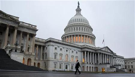 A man walks past the U.S. Capitol Building in Washington December 17, 2012. The first real movement in the ''fiscal cliff'' talks began on Sunday, with Republican House Speaker John Boehner edging slightly closer to President Barack Obama's key demands as they try to avert the steep tax hikes and spending cuts set to take effect unless Congress intervenes by December 31. REUTERS/Joshua Roberts (UNITED STATES - Tags: POLITICS BUSINESS)