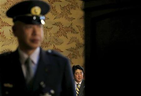 Japan's conservative Liberal Democratic Party's (LDP) leader and next Prime Minister Shinzo Abe (R) is seen behind a security guard as he attends a meeting with New Komeito's party leader Natsuo Yamaguchi (not pictured) at the Parliament in Tokyo December 18, 2012. Abe said on Tuesday that he has asked Bank of Japan Governor Masaaki Shirakawa to consider establishing a 2 percent inflation goal. REUTERS/Toru Hanai (JAPAN - Tags: BUSINESS POLITICS)