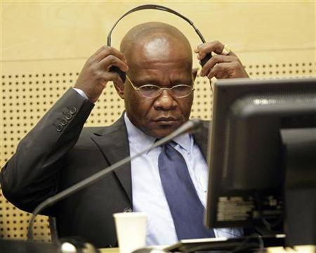 Congolese warlord Mathieu Ngudjolo Chui puts on his headset in the courtroom of the International Criminal Court in The Hague November 24, 2009. REUTERS/Michael Kooren/Files