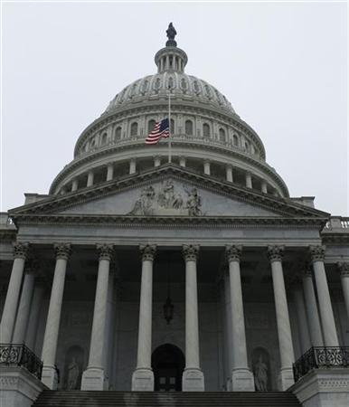 The United States flag flies at half staff in front of the U.S. Capitol dome in Washington December 17, 2012. REUTERS/Gary Cameron (UNITED STATES - Tags: POLITICS CRIME LAW)