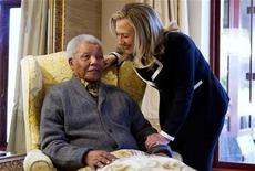 """El ex presidente sudafricano Nelson Mandela """"está mucho mejor"""" luego de ser tratado por una infección pulmonar y cálculos biliares, dijo el martes un portavoz de la presidencia, aunque los médicos mantendrían al carismático líder en el hospital por el momento para darle cuidados adicionales. En la imagen, la secretaria de Estado estadounidense Hillary, Clinton, se reúne con Nelson Mandela, en su casa de Qunu, en Sudáfrica, el 6 de agosto de 2012. REUTERS/Jacquelyn Martin/Pool"""