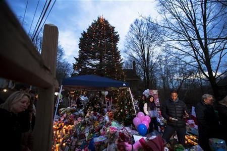 Mourners walk around a journalist (2nd R) at a memorial dedicated to the victims of the shooting at Sandy Hook Elementary School in Sandy Hook Village in Newtown, Connecticut, December 18, 2012. REUTERS/Lucas Jackson