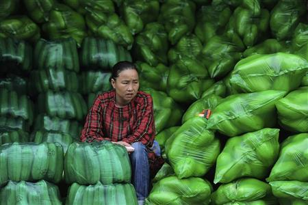 A vendor sits by piles of packaged vegetables at a market in Hefei, Anhui province October 11, 2011. REUTERS/Stringer/Files