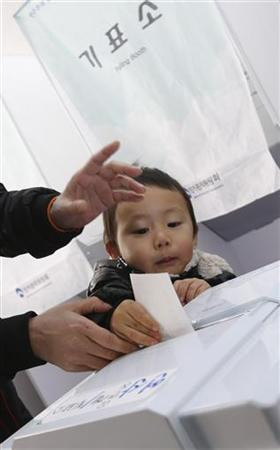 A woman casts her ballot with her child in the presidential election at a polling station in Nonsan, about 190 km (118 miles) south of Seoul, December 19, 2012. More than 40 million people are eligible to vote in the presidential election of the country on Wednesday to elect a winner who will take office in February for the mandatory five year single term. REUTERS/Lee Jae-Won (SOUTH KOREA - Tags: POLITICS ELECTIONS)