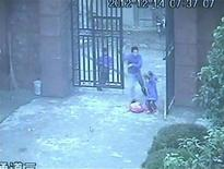 A man (C), waving a knife in his hand, chases a girl (R) as he enters an elementary school in Guangshan county, Henan province, in this still image from a December 14, 2012 surveillance video, released by local police December 18, 2012. Authorities on Monday confirmed the arrest of the 36-year-old Chinese man, Min Yongjun, suffering from epilepsy in connection with last Friday's knife attack at the elementary school. Min burst into an elderly woman's house near the school and stabbed her with a knife before rushing to the school and attacked more than 20 children, according to Ouyang Mingxing, deputy director of the Public Security Bureau of Guangshan County. Video taken December 14, 2012. REUTERS/CCTV via Reuters TV