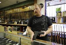 Vendedor Eric Grabowski mostra arma em uma loja, em Wisconsin. Fabricantes de armas dos EUA enfrentam pressões de alguns grandes investidores depois do massacre da semana passada em uma escola primária de Connecticut. 07/08/2012 REUTERS/John Gress