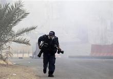 Un photographe se mettant à couvert lors d'affrontements au Bahreïn. L'année 2012 a été la plus meurtrière pour les journalistes depuis 1995 et le premier bilan annuel de Reporters sans frontières. /Photo prise le 24 mars 2012/REUTERS/Ahmed Jadallah