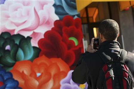 Carl Fisher uses a phone to snap a picture of a mural in the Mission District in San Francisco, California December 18, 2012. REUTERS/Robert Galbraith