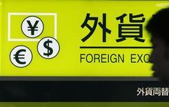 """Человек проходит мимо вывески обменного пункта в токийском аэропорту """"Ханэда"""" 1 августа 2011 года. Иена немного повысилась в четверг после того, как Банк Японии объявил о смягчении денежной политики, расширив скупку активов на 10 триллионов иен и пообещав отрегулировать инфляционный ориентир. REUTERS/Yuriko Nakao"""
