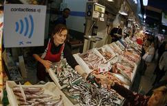 Los ministros de pesca de la Unión Europea cerraron el jueves un acuerdo que en su opinión refleja un compromiso con la protección de los caladeros sobreexplotados, como los del abadejo y la platija, y la salvaguarda del modo de vida de los pescadores. En la imagen, una mujer vende pescado en un mercado de Palma de Mallorca el 18 de diciembre de 2012. REUTERS/Enrique Calvo
