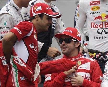 Ferrari Formula One driver Felipe Massa of Brazil (L) and team mate Fernando Alonso of Spain get ready for a group photo before the Brazilian F1 Grand Prix at Interlagos circuit in Sao Paulo November 25, 2012. REUTERS/Ricardo Moraes