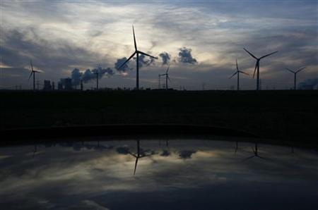 Wind generators and the Niederaussem coal power plant of RWE Power, one of Europe's biggest electricity and gas companies, are reflected in the roof of a car in Rheidt, north-west of Cologne October 11, 2012. REUTERS/Wolfgang Rattay