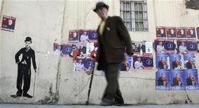 Мужчина проходит мимо предвыборных плакатов в Тбилиси 27 мая 2010 года. Парламент Грузии вечером в четверг утвердил бюджет на 2013 год с увеличенными расходами на социальные нужды, а также здравоохранение и развитие агросектора, что отражает предвыборные обещания коалиции нынешнего премьер-министра страны Бидзины Иванишвили, одержавшей победу на парламентских выборах 1 октября. REUTERS/David Mdzinarishvili