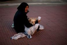 Casi 23.000 personas sin hogar fueron atendidas en 2012 en centros asistenciales en España, la mayoría de ellas hombres españoles menores de 45 años que perdieron su casa tras quedarse sin empleo, según informó el viernes el Instituto Nacional de Estadística (INE). En esta imagen de archivo, una mujer mendiga con su perro en una calle del centro de Málaga, el 28 de noviembre de 2012. REUTERS/Jon Nazca