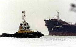 Греческий танкер Stemnitsa (справа) выходит из Приморского торгового порта 5 февраля 2003 года. Крупнейший российский портовый оператор Группа НМТП нарастил чистую прибыль по международным стандартам за 9 месяцев 2012 года на 345 процентов до $320 миллионов, сообщила компания в пятницу. REUTERS/Alexander Demianchuk