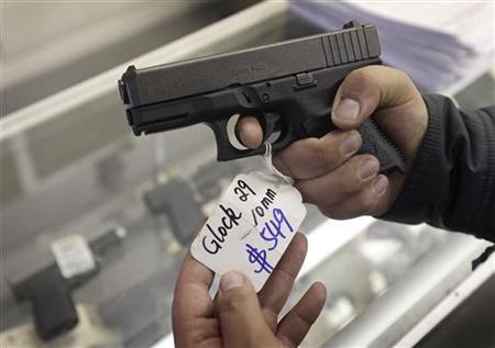 A customer looks over a Glock 29 10mm hand gun at the Guns-R-Us gun shop in Phoenix, Arizona, December 20, 2012. REUTERS/Ralph D. Freso