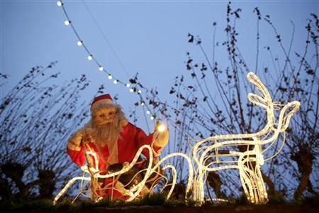 A Santa Claus figure is illuminated at a Christmas market in the city centre of Frankfurt December 20, 2012. REUTERS/Lisi Niesner