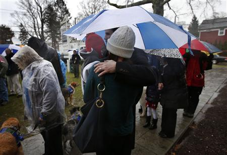 People stand in a driving rain outside the Edmond Town Hall during a moment of silence and ringing of church bells at 9:30am EDT for the victims of the December 14 shooting at the Sandy Hook Elementary school in Newtown, Connecticut, December 21, 2012. REUTERS/Mike Segar