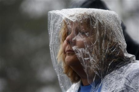 A woman stands in driving rain outside the Edmond Town Hall in the center of Newtown, Connecticut during a moment of silence and ringing of church bells for the victims of the December 14 shooting at the Sandy Hook Elementary school in Newtown, Connecticut, December 21, 2012. REUTERS/Mike Segar