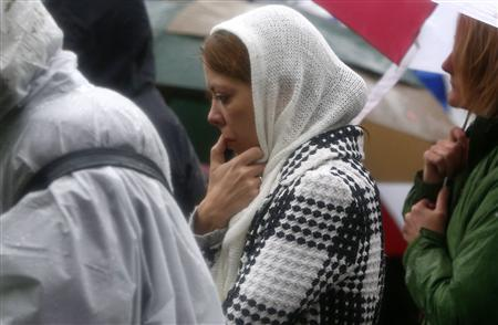 People stand in driving rain outside the Edmond Town Hall in the center of Newtown, Connecticut during a moment of silence and ringing of church bells for the victims of the December 14 shooting at the Sandy Hook Elementary school in Newtown, Connecticut, December 21, 2012. REUTERS/Mike Segar