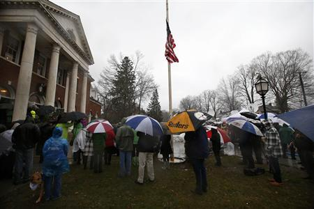 People stand in a driving rain outside the Edmond Town Hall during a moment of silence and ringing of church bells at 9:30am EDT for the victims of the December 14 shootings at the Sandy Hook Elementary school in Newtown, Connecticut, December 21, 2012. REUTERS/Mike Segar