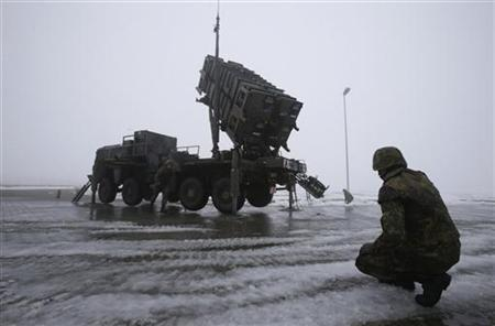 Soldiers of the German armed forces Bundeswehr stand next to a PAC-2 launcher of a ''Patriot'' missile battery during a media rehearsal in the north German village of Warbelow December 18, 2012. REUTERS/Tobias Schwarz