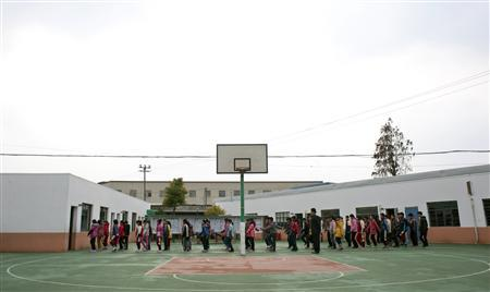 Students line up doing exercise on playground at a primary school for children of migrant workers in Shanghai, December 18, 2012. REUTERS/Darcy Holdorf
