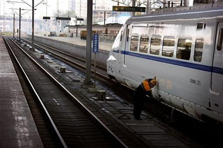 A railway worker fills the water tanks of a train as it prepares to leave the central railway station of the Chinese city of Zhengzhou, Henan Province October 30, 2012. REUTERS/David Gray/Files