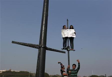 Demonstrators shout slogans and carry a placard while standing on lamp posts during a protest rally near the presidential palace in New Delhi December 22, 2012. Indian police used batons, tear gas and water cannon to turn back thousands of people marching on the presidential palace on Saturday in intensifying protests against the gang-rape of a woman on the streets and on social media. REUTERS/Ahmad Masood (INDIA - Tags: CRIME LAW CIVIL UNREST)