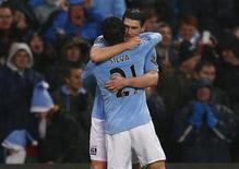 Manchester City a buté pendant 92 minutes sur Reading samedi dans son Etihad Stadium, avant de faire plier le dernier de la Premier League grâce à un but de Gareth Barry (ici avec son coéquipier David Silva) à la fin du temps additionnel (1-0). /Photo prise le 22 décembre 2012/REUTERS/Darren Staples
