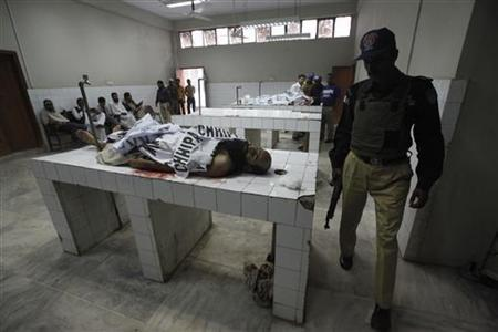 A policeman walks past the body of a man killed during an operation against the suspected killers of anti-polio workers in Sohra Goth area in Karachi December 19, 2012. REUTERS/Athar Hussain