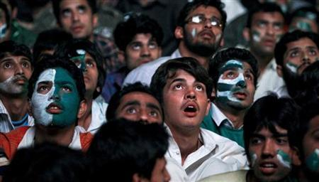 Pakistanis react while watching on a large screen their national team play India during a ICC Cricket World Cup semi-final match, in Islamabad March 30, 2011. REUTERS/Faisal Mahmood/Files