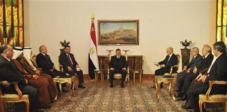 Egypt's President Mohamed Mursi (C) meets with members of the Organization of Arab Petroleum Exporting Countries (OAPEC) at the presidential palace in Cairo December 22, 2012. REUTERS/Egyptian Presidency/Handout